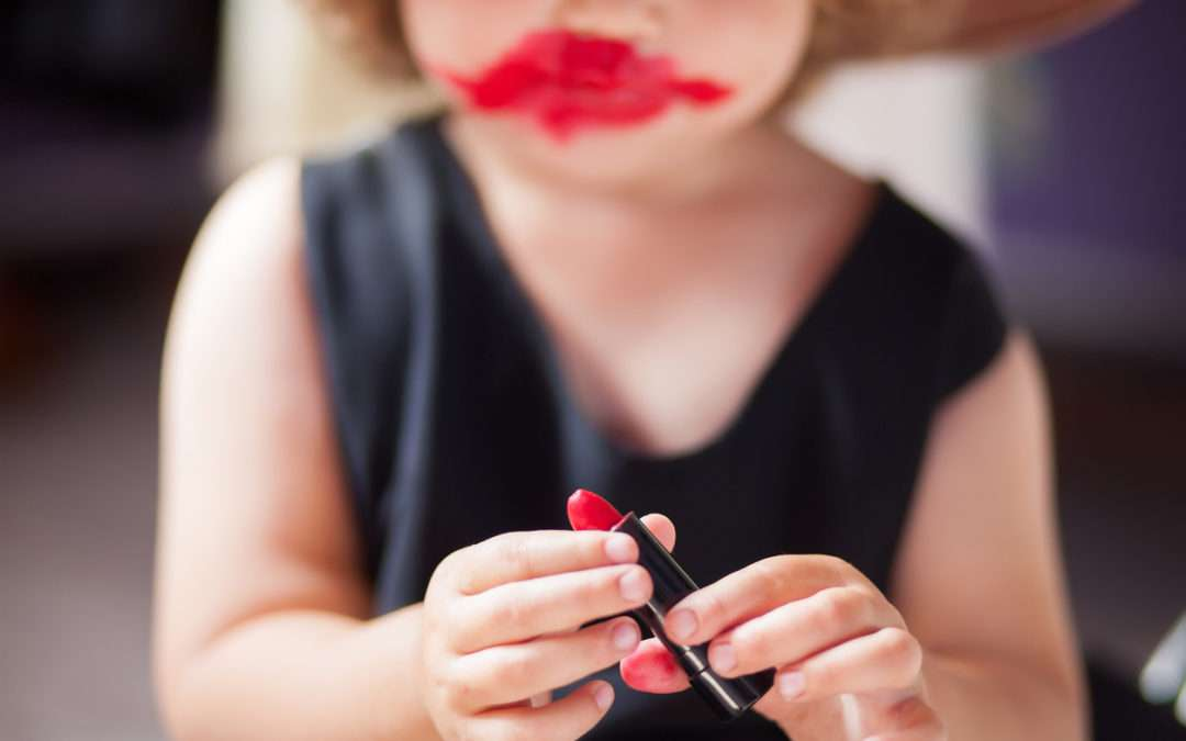 little girl making mess with mother's lip stick